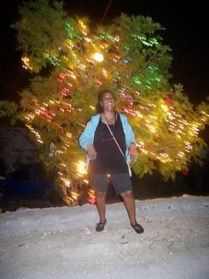 Tamika beside Ackee Christmas Tree